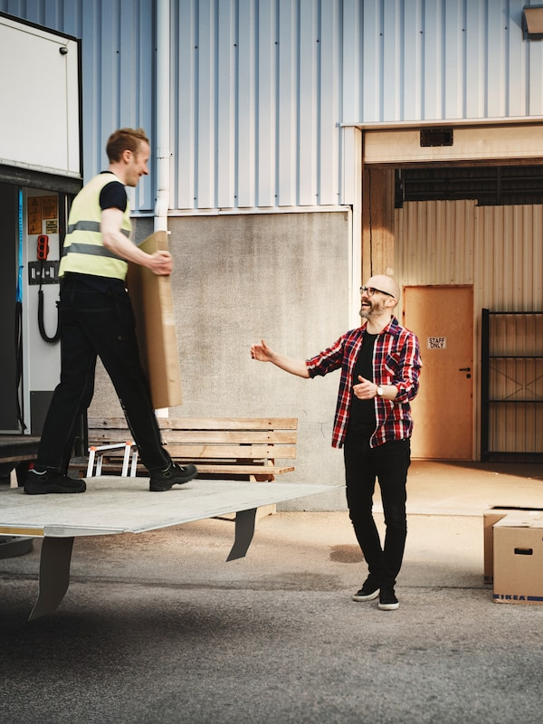 A man with a beard and glasses waiting to take an item from another man on the back of a delivery truck.