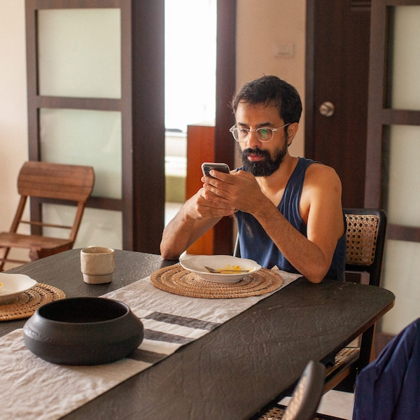 A man with dark hair and a beard just finished eating and is browsing his mobile phone at the kitchen table.