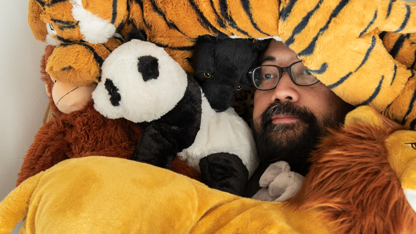 A man with glasses and a beard lies among a whole bunch of DJUNGELSKOG soft toys. Only his face shows.