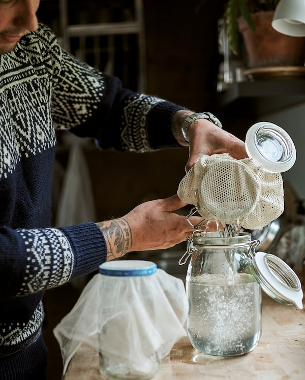 A man works at a kitchen bench, pouring clear liquid from one Kilner-style jar to another using muslin as a strainer.