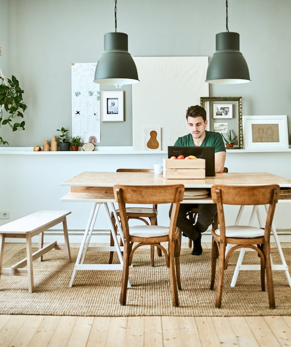 A man works on a laptop at a wood table, two grey pendant lamps hang above with a display of pictures on a grey wall behind.