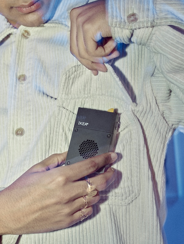 A man's hand attaching a wearable portable black mini speaker to the pocket of his beige corduroy shirt.