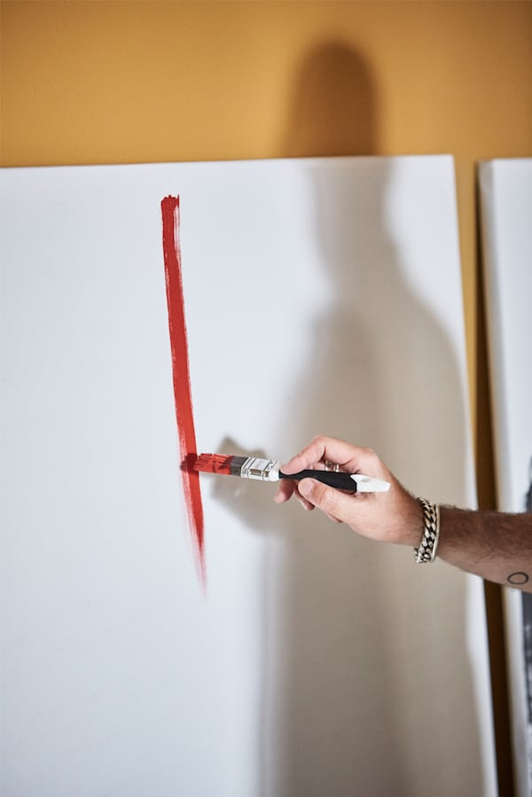 A man's hand holding a paintbrush and painting a red line on a white canvas leaning on an ochre wall with person's shadow.