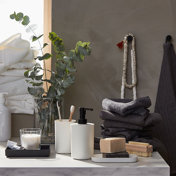 A marble bathroom counter with sprigs of eucalyptus, a stack of gray towels, and white bathroom accessories.