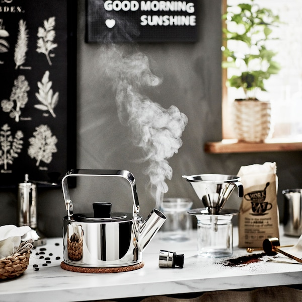 A marble kitchen counter with a steaming kettle, metal coffee filter, and an open bag of PÅTÅR coffee.