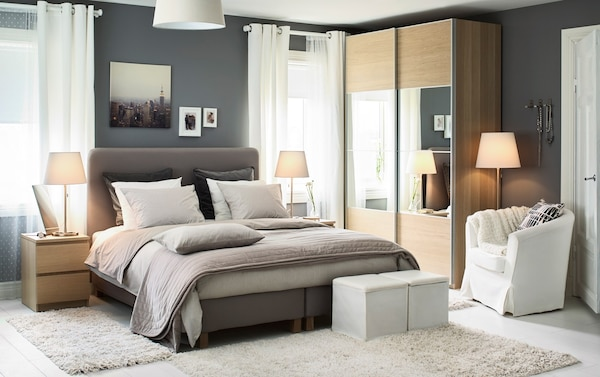 A medium bedroom with IKEA LAUVIK dark beige divan bed and two wood coloured chest of drawers used as bedside tables.