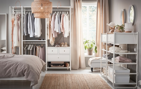 A medium sized bedroom furnished with open floor-to-ceiling ELVARLI storage, consisting of white shelves and clothes.