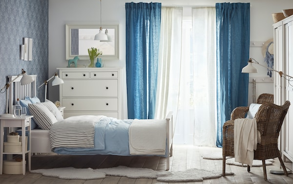 A medium sized bedroom with a white bed for two with bedlinen in light blue and grey. Shown together with a white chest of drawers, mirror and two bedside tables.