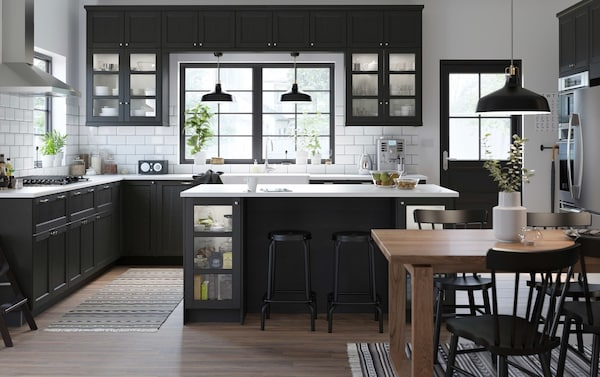A medium sized black and white traditional styled kitchen with stained black LERHYTTAN kitchen cabinet doors.