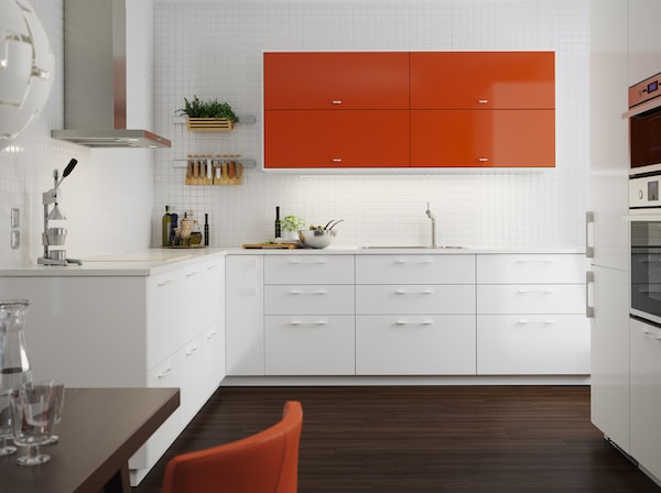 A medium sized kitchen with orange high-gloss doors combined with white high-gloss doors and drawers. Shown together with stainless steel appliances.