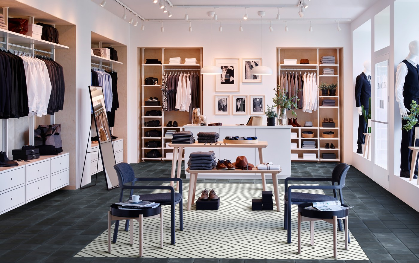 A men's clothing store with four IKEA ELVARLI storage units around the room, with two LISABO light wood tables in the centre.