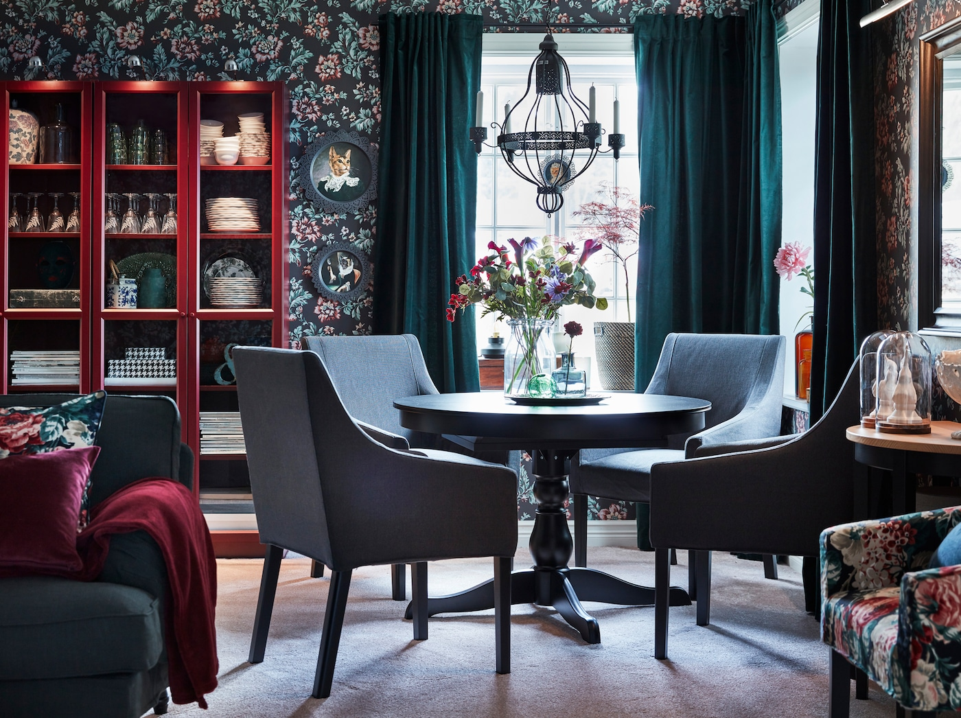 A mesa extensível redonda em preto INGATORP e as cadeiras SAKARIAS em padrões cinzentos e florais combinam com o papel de parede floral vintage e com os cortinados de veludo em verde escuro do espaço de refeição.