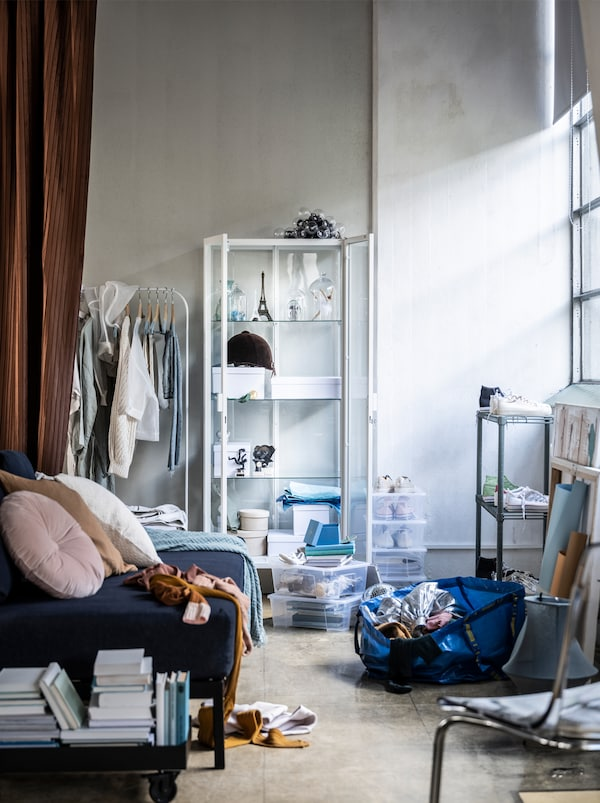 A messy room with sofa, white shelving unit, curtain, stacked books, an IKEA blue bag of stuff on the floor and window light.