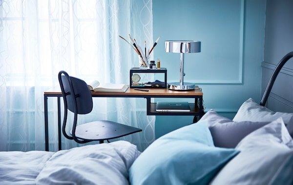 A metal and solid wood laptop table with castors and a swivel chair in the small space between a bed and a wall.