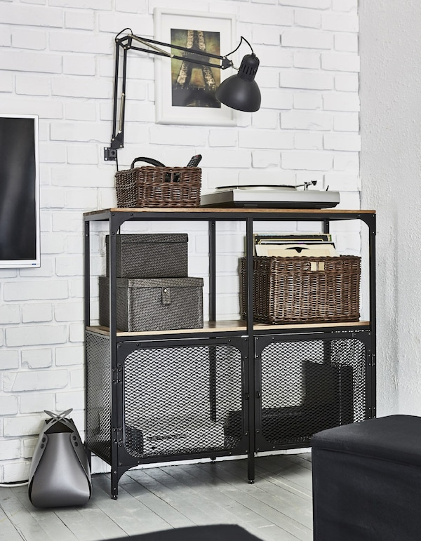 A metal FJÄLLBÖ shelving unit stores entertainment equipment like remotes and cables in a living room.