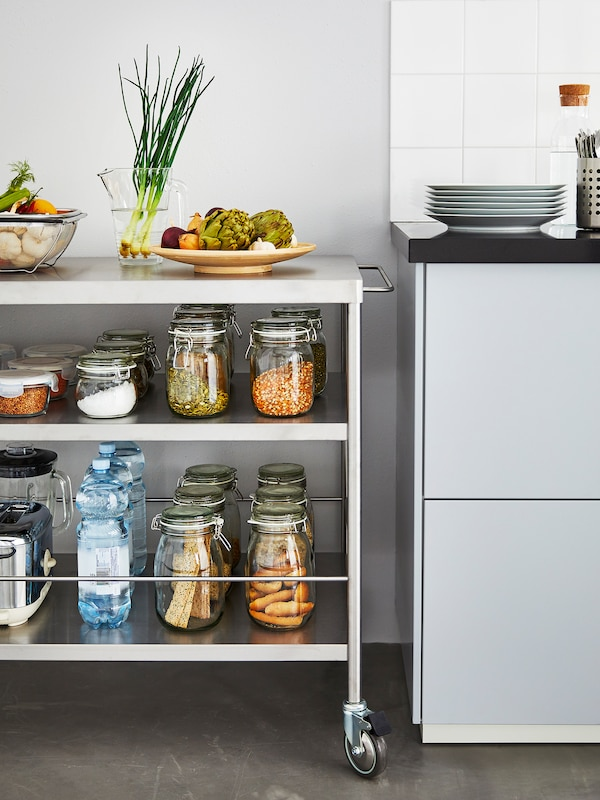 A metal kitchen island stands next to a kitchen counter storing several glass jars with dry goods and vegetables.