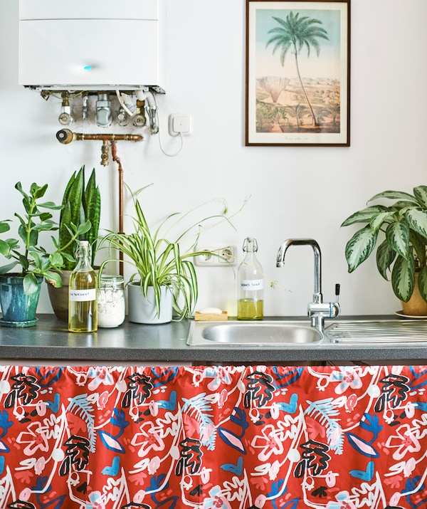 A metal sink with plants and bottles filled with liquid on top. Red patterned fabric covers under the sink.