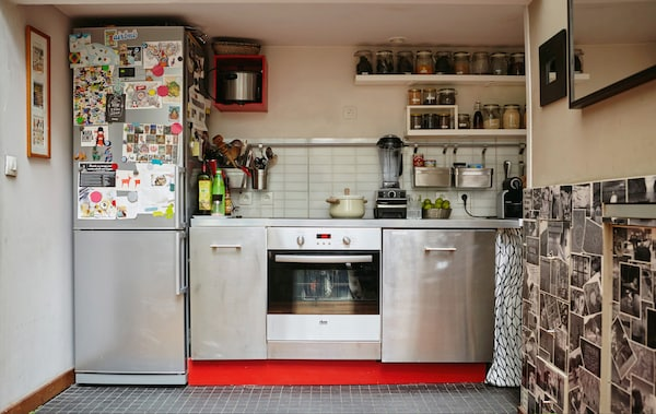 A metallic kitchen along one wall and a fridge freezer with magnets