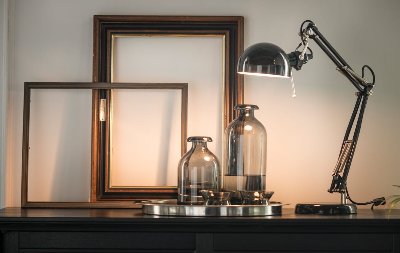 A metallic lamp, glass bottles, and empty frames arranged on top of a black cabinet.