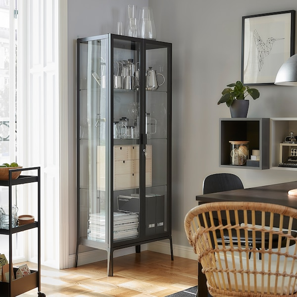A MILSBO glass-door cabinet stands next to a balcony door. Decorative items, magazines and magazine files are stored inside.