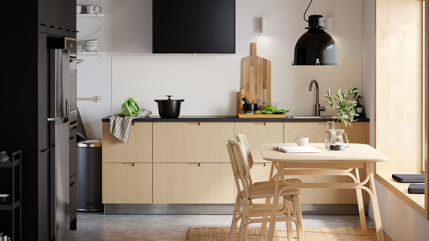 A minimalist kitchen with light bamboo drawer fronts, black doors, a light bamboo dining table and two chairs.
