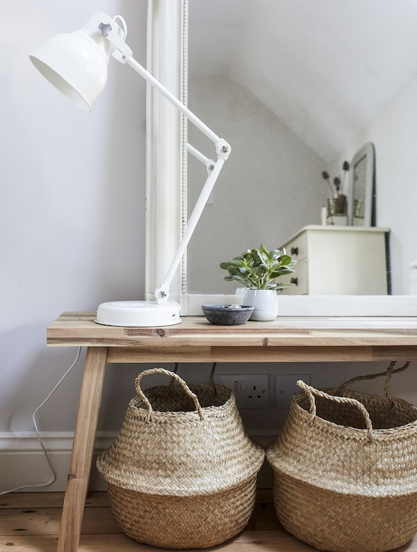 A mirror and lamp on top of a wooden bench with two storage baskets underneath.