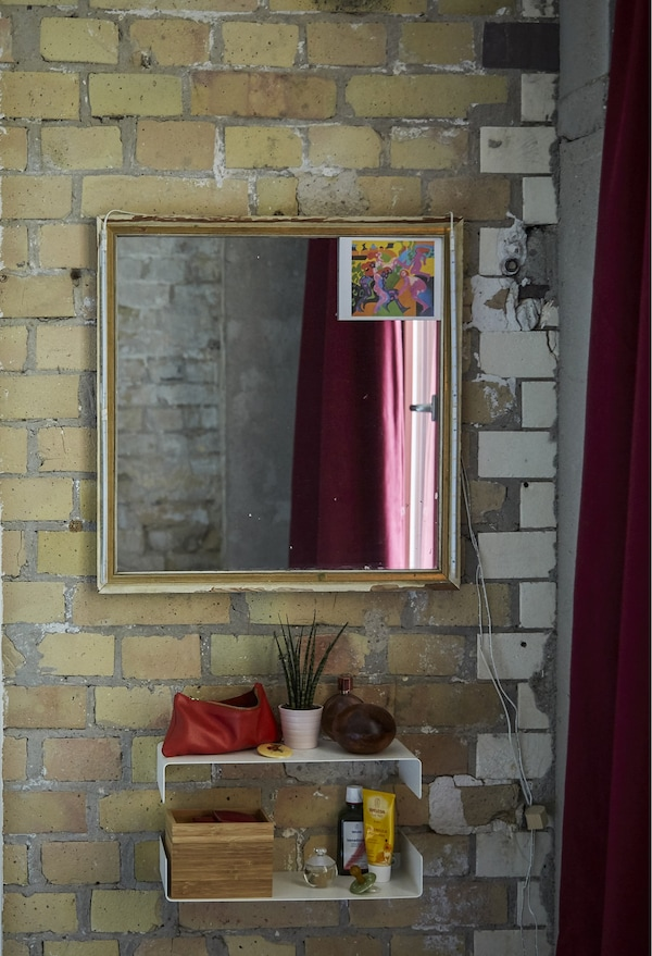 A mirror and shelves on a brick wall.