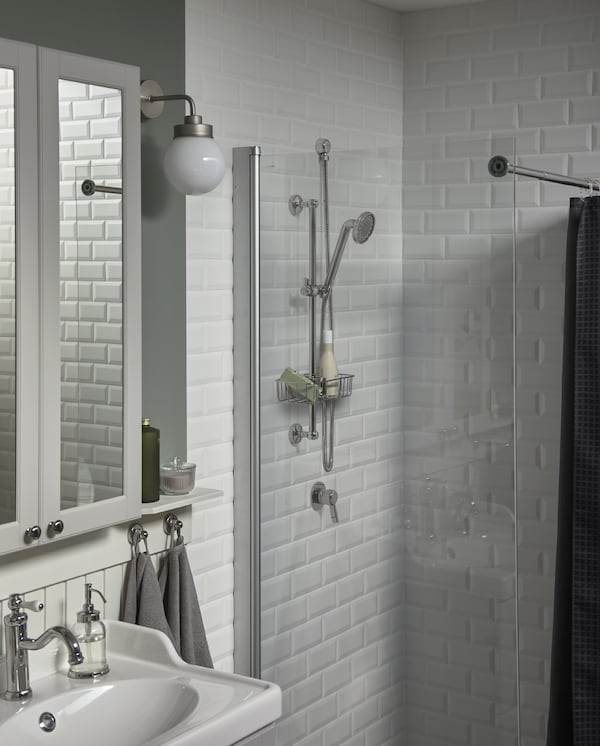 A mirror cabinet and wash-basin in white, a white-tiled shower and a head shower and a shower shelf that are chrome-plated.