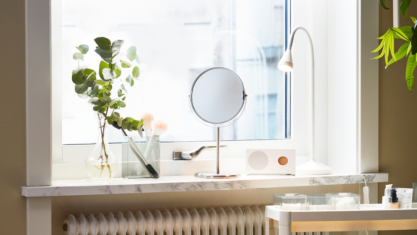 A mirror placed on a window sill, with a white table lamp, a green sprig in a vase and a Bluetooth speaker on the sill.