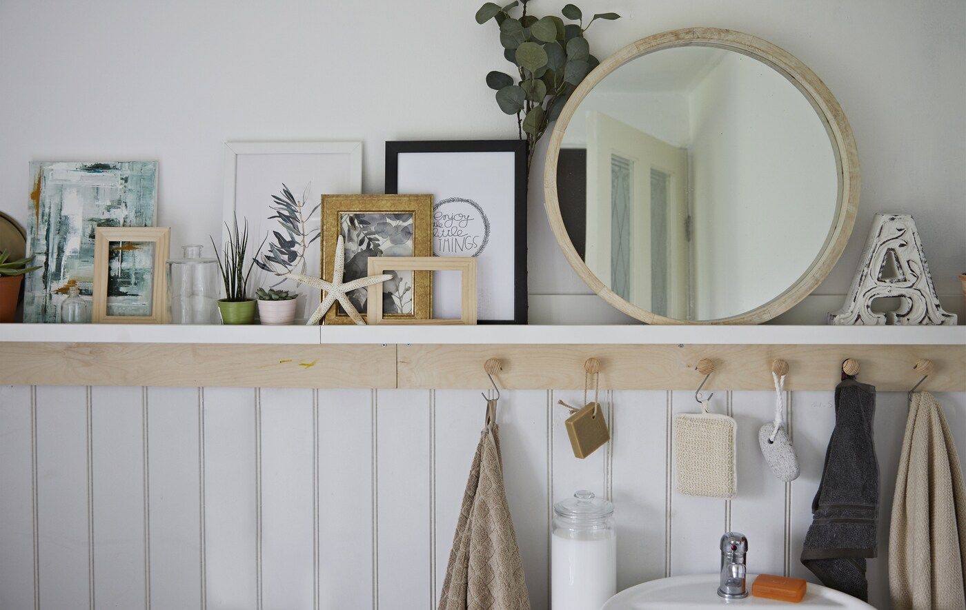 A mirror, plants, pictures and shells on a bathroom shelf with hooks underneath.