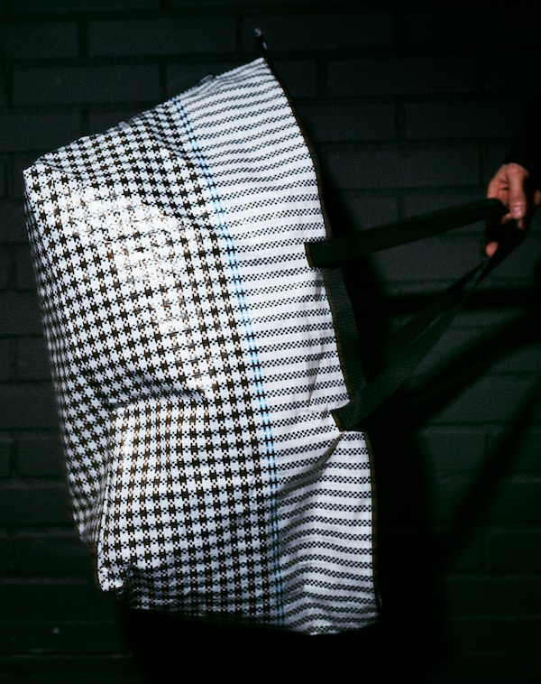 A model holds the SAMMANKOPPLA bag in a dark room. Its shiny texture and checked pattern is shown by the camera flash.