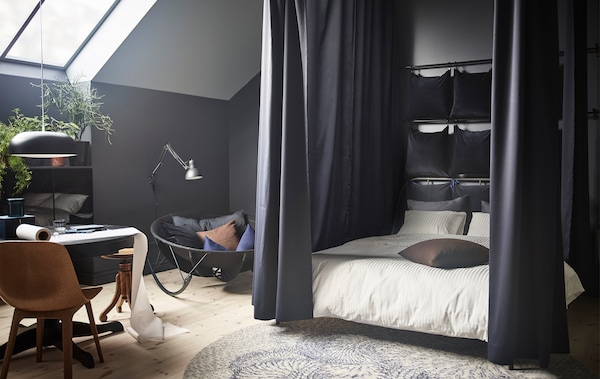 A modern bedroom with dark walls, bed curtains, a reading nook, and table for eating or working.