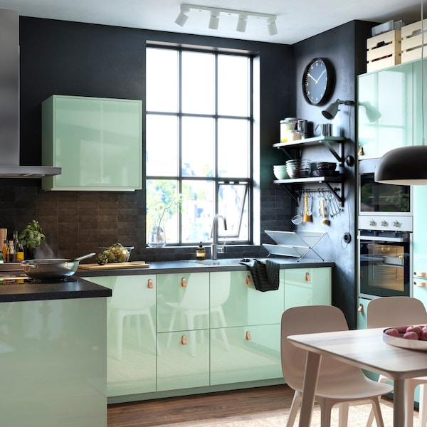 A modern black and green kitchen with retro vibe thanks to KALLARP doors in high-gloss light green and leather handles.