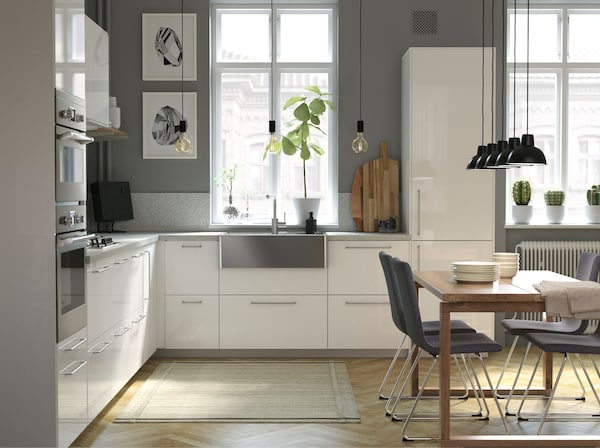 A modern, bright IKEA METOD kitchen, with white high gloss RINGHULT doors and drawers, with stainless steel sink bowl, in an open living space.