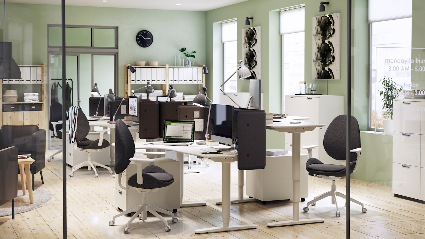 A modern furnished office environment with light green walls and white BEKANT adjustable corner desks and chairs.
