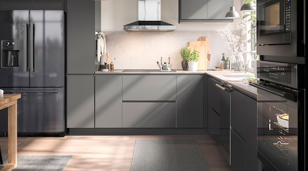 A modern gray kitchen with black stainless steel appliances