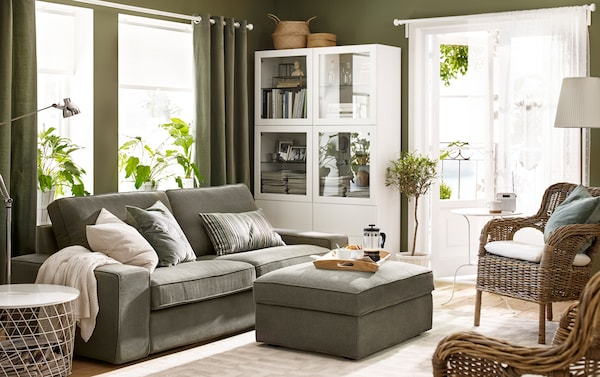 A modern grey-green three-seat sofa with footstool in a living room with green walls.