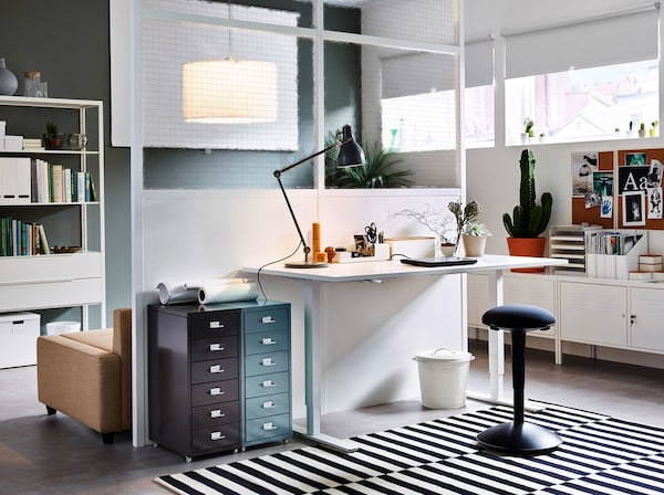 A modern home office with a white IKEA SKARSTA adjustable work desk and ALEX rollable cabinet drawers on castors.