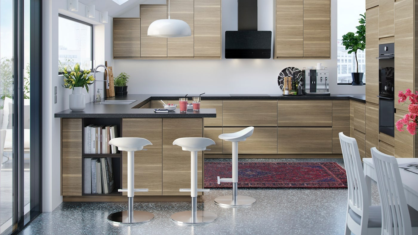 A modern kitchen with VOXTORP kitchen fronts in walnut-effect, with three white JANINGE bar stools and NYMÅNE pendant lamp.