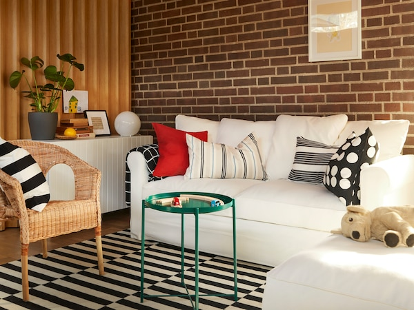 A modern living room with a cream GRÖNLID sofa bed and a chaise lounge on a striped STOCKHOLM rug.