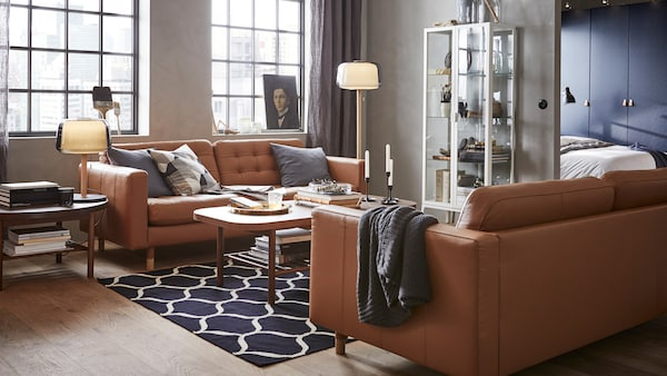 A modern living room with a glass storage cabinet, brown leather sofas and round dark wooden coffee tables.
