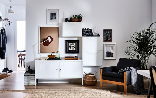A modern living room with one wall furnished with three TRONES shoe cabinets aligned around a bench to create storage and focal points