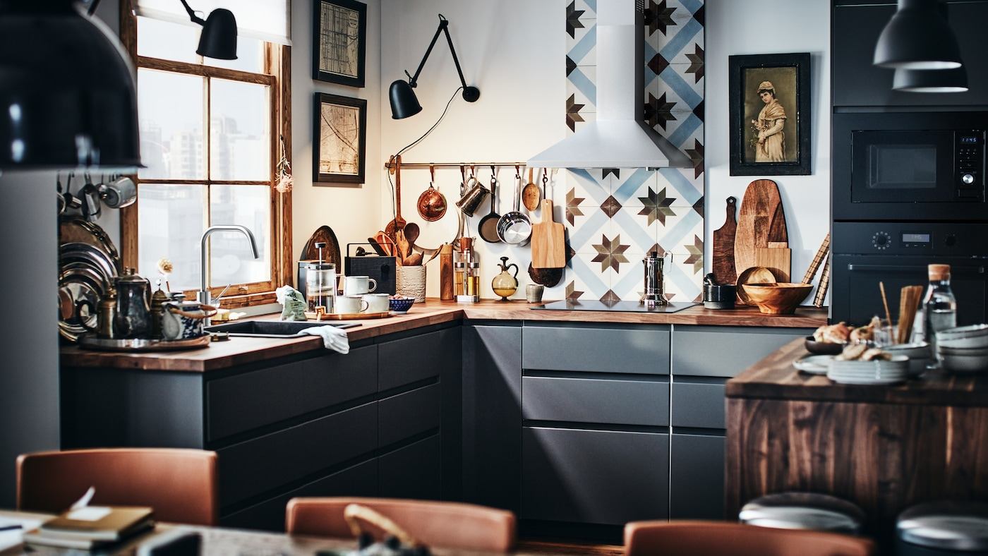 A modern METOD kitchen with dark gray fronts and a wooden worktop with a kitchen tile backsplash.