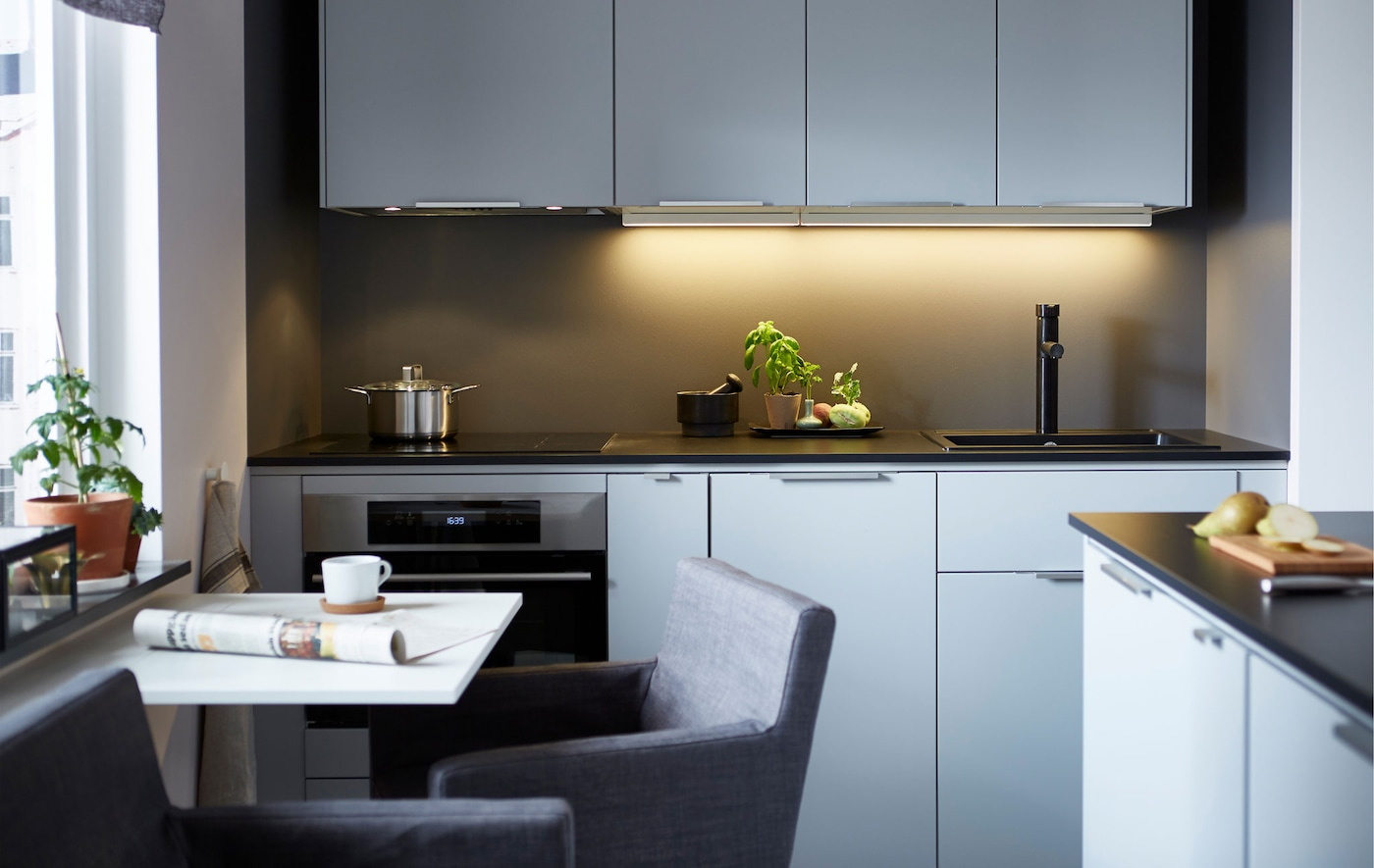 A modern, sleek kitchen with a wall of light-colored cabinets, dark counter tops and a small dining table.