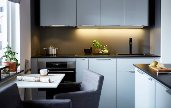 A modern, sleek kitchen with a wall of light-coloured cabinets, dark counter tops and a small dining table