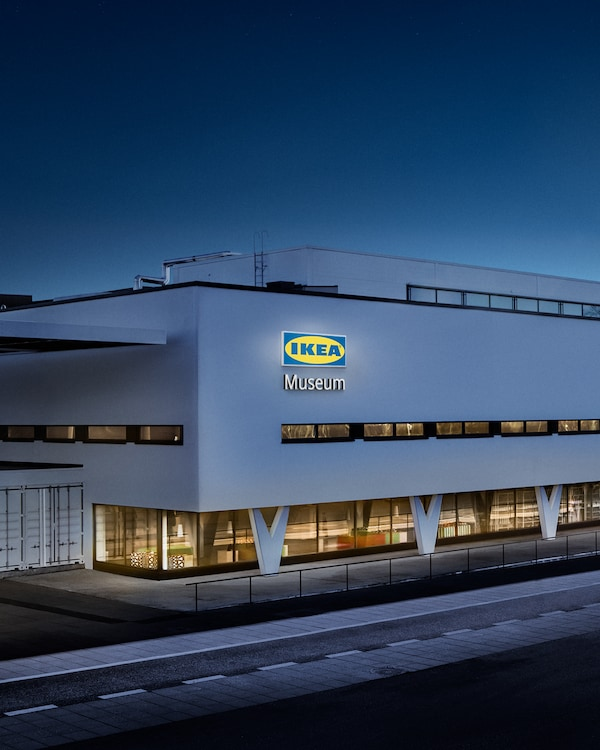 """A modern white building is pictured at night with """"IKEA Museum"""" lit up on the side."""