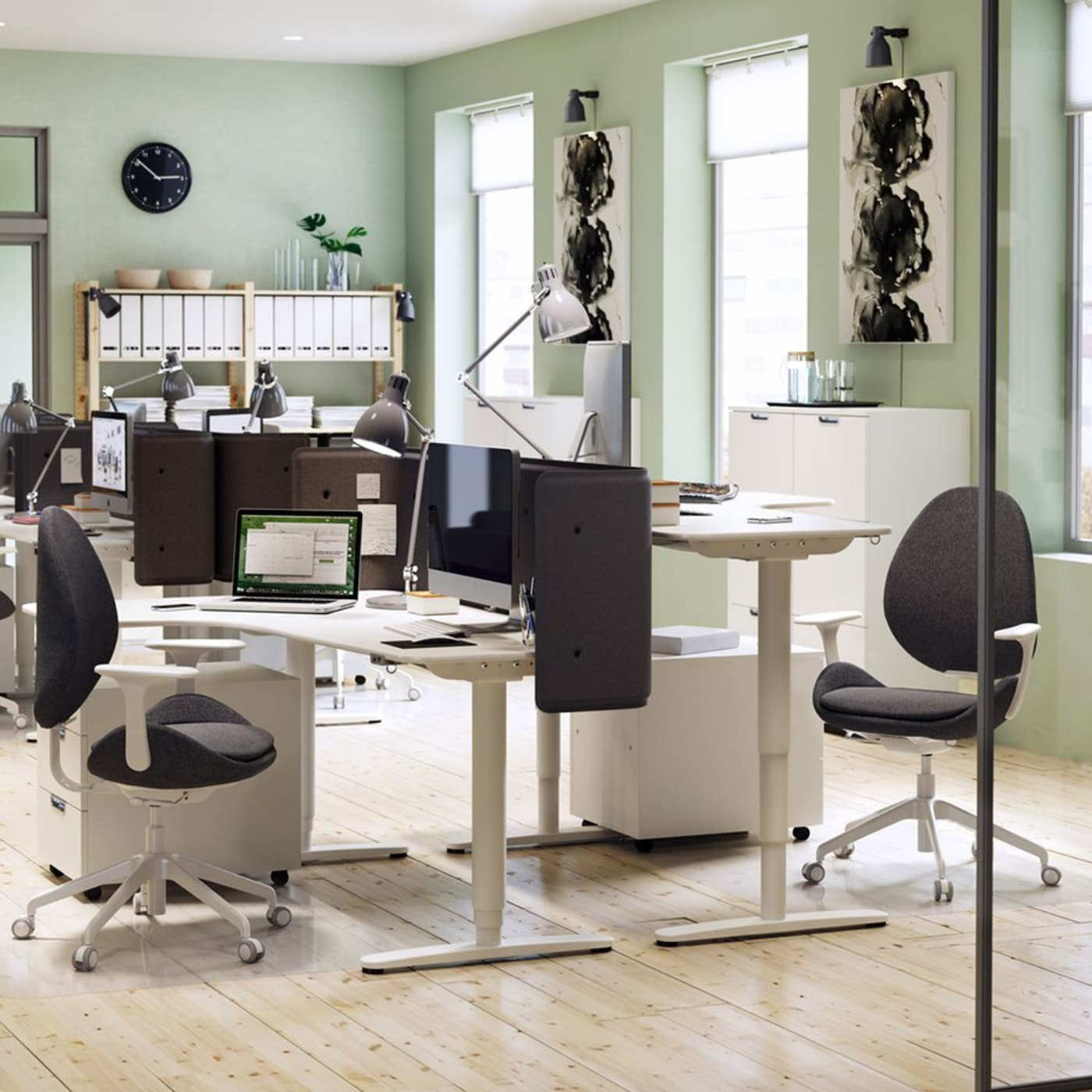 A modernly furnished office environment with light green walls and white IKEA BEKANT adjustable corner desks.