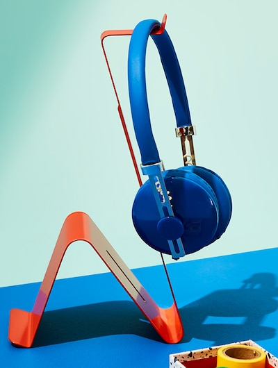 A MÖJLIGHET Headset/tablet stand with headphones hanged on it.