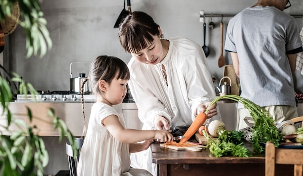 a mom and kid are cutting carrot