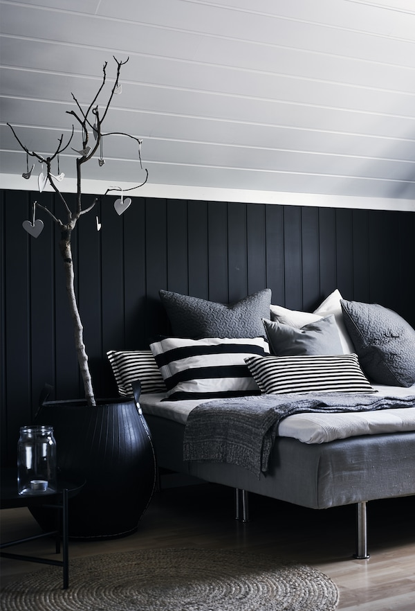 A monochrome bed with cushions.
